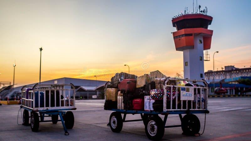 Diagram av bagage som är klara att laddas in i flygplanet framme av flygtrafikkontrollanten royaltyfria bilder