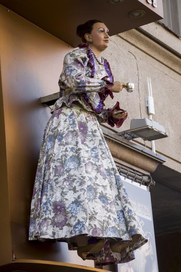 Diagram av kvinnan i härlig klänning med en kopp av välkomna gäster för utslagsplats eller för coffe Dockan på väggen av shoppar royaltyfria foton