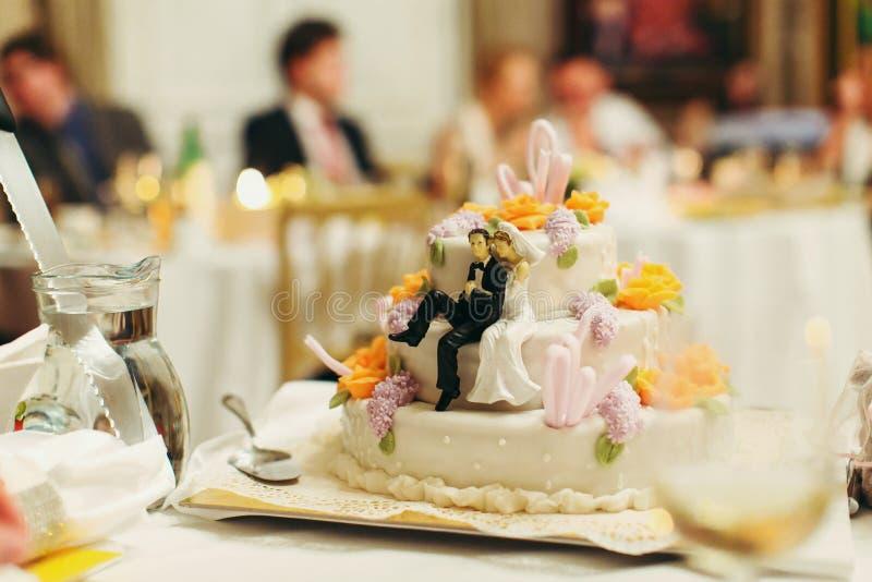 Diagram av nygifta personer sitter på den smakliga bröllopstårtan fotografering för bildbyråer