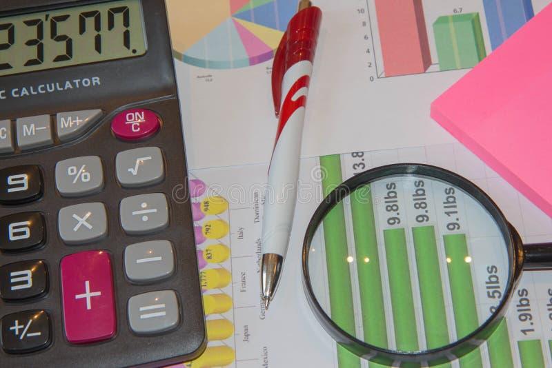 Diagram räknemaskin, förstoringsapparat och penna Analysering av finansiella data och räkna på räknemaskinen royaltyfria bilder
