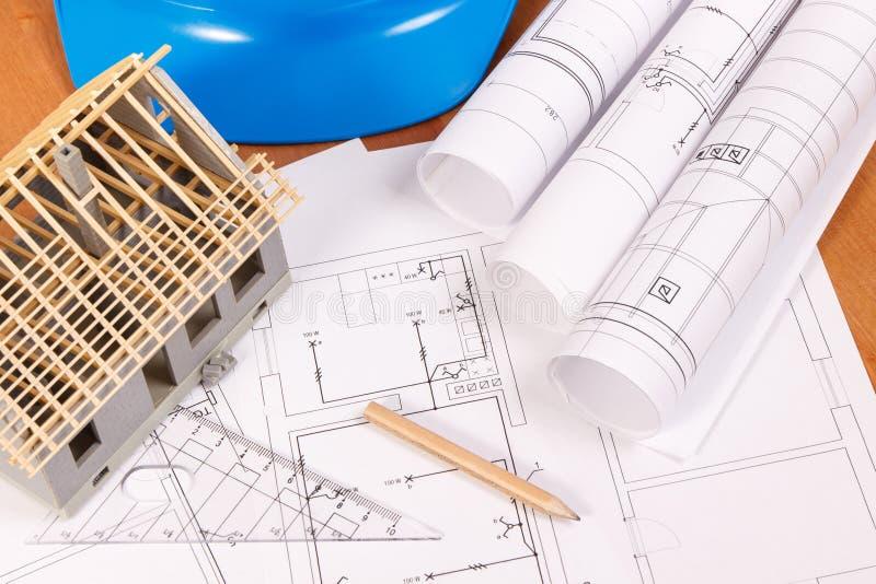 Diagramas bondes, acessórios para trabalhos do coordenador e casa sob a construção na mesa, conceito home de construção foto de stock