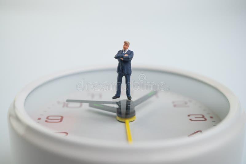 Diagramet affärsmän är tänka och stå på den vita klockaframsidan av klockaframsidan som visar tiden Begrepp av tidmanagemen arkivfoto