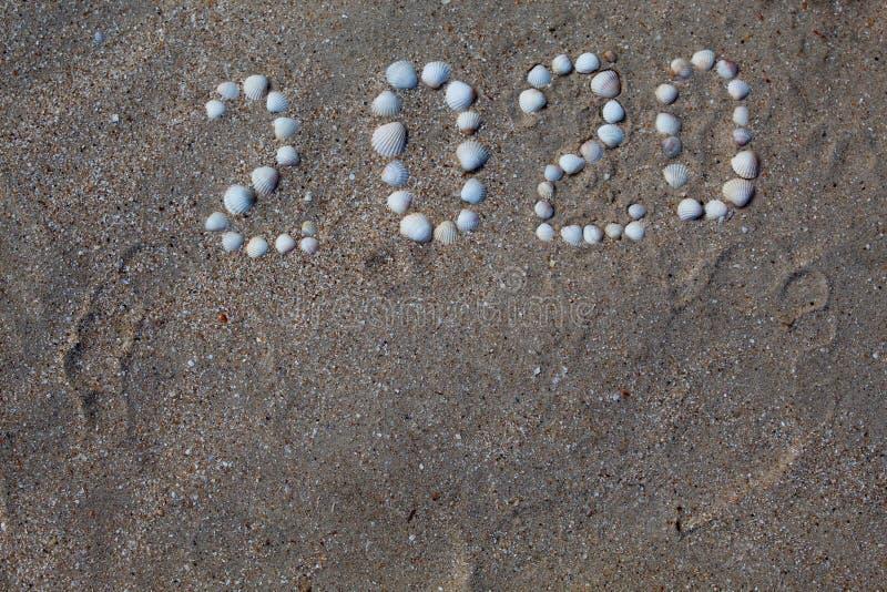 Diagramet '2020 'läggas ut på sand med skal arkivfoton
