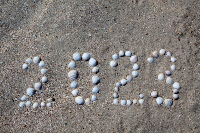 Diagramet '2023 'läggas ut på sand med skal arkivbild
