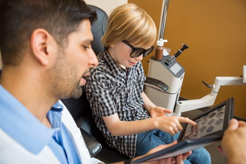 Diagramme d'essai de lecture de garçon tandis qu'optométriste photos stock