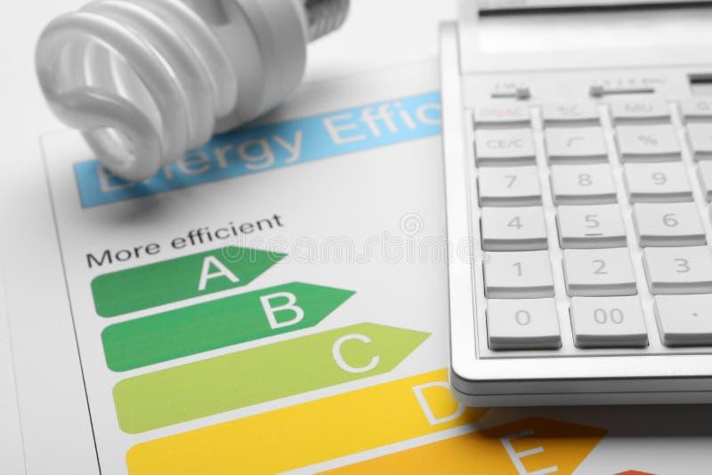 Diagramme d'estimation de rendement énergétique, ampoule fluorescente et calculatrice photo stock
