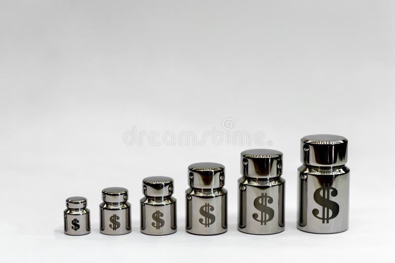 Diagramme des poids en m?tal avec le laser gravant des symboles du dollar sur un fond gris-clair image stock