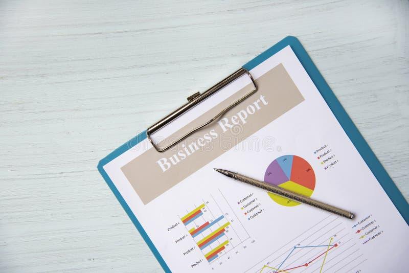 Diagramme et stylo de graphique de rapport de gestion sur le présent de document sur papier de rapport financier sur le fond de  photographie stock libre de droits