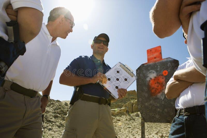 Diagramme masculin de cible de Holding Clipboard With d'instructeur photos libres de droits