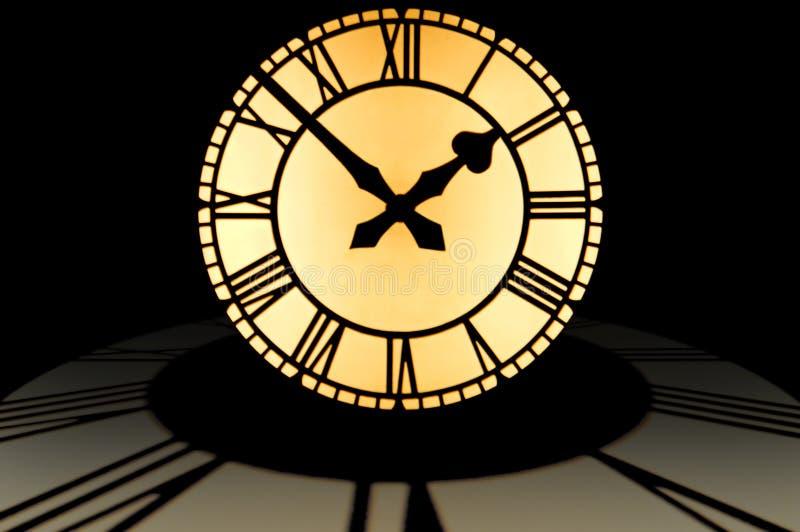 Dial de reloj iluminado grande a diez a las dos encima de un círculo de imagen de archivo libre de regalías