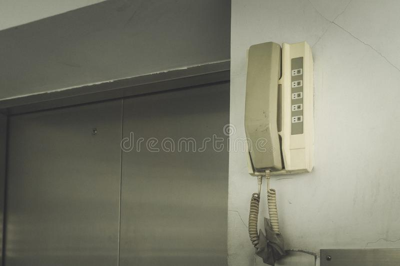 Dial the emergency analog telephone hanging on the wall at the elevator. With copy space for text stock image