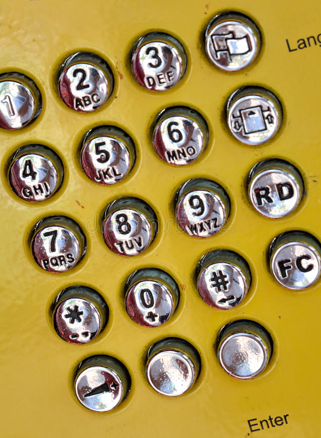 Dial plate of public telephone. Dail plate keyboard of public telephone in metal, with sliver and yellow color, shown as communication and numberic stock image