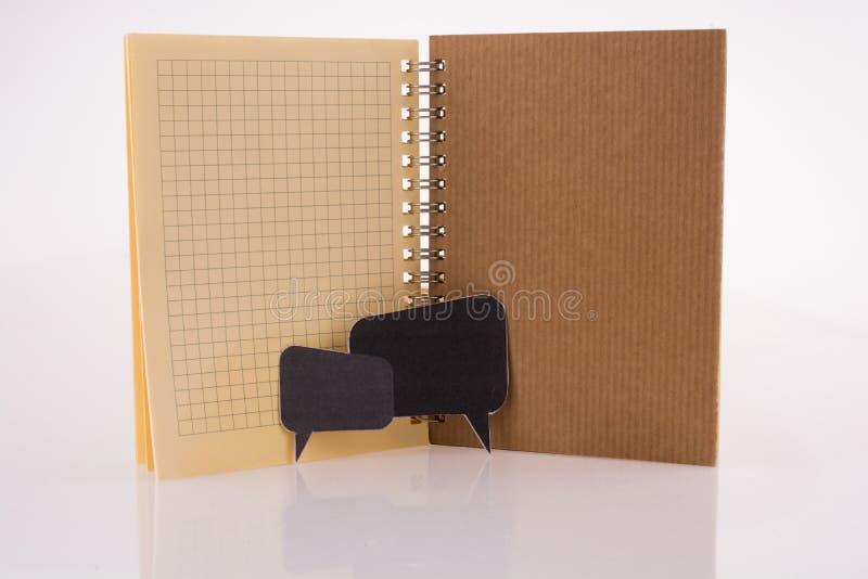 Dialogue boxes near a notebook royalty free stock photos