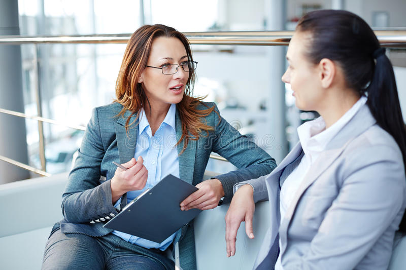 Dialogue. Pretty young manager explaining business partner her view of the problem stock photography