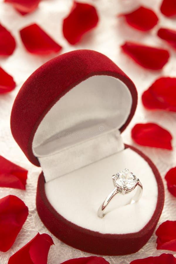 Diamant-Ring im Kasten umgeben von Rose lizenzfreie stockfotografie