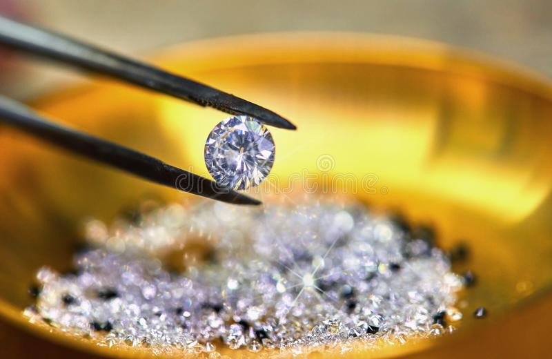 Diamant som rymms av pincett mot bakgrunden arkivbild