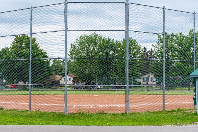 Diamante del béisbol o del softball a través de una cerca en parque en una ciudad canadiense de la pequeña ciudad de Brighton cer imagenes de archivo