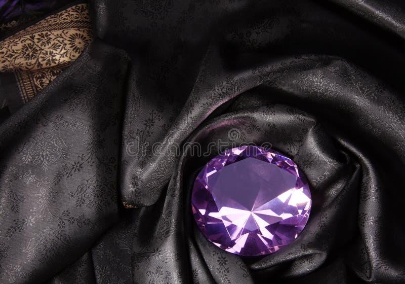 Diamante rosado en la tela negra fotografía de archivo libre de regalías