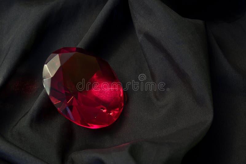 Diamante rosso su raso nero fotografie stock