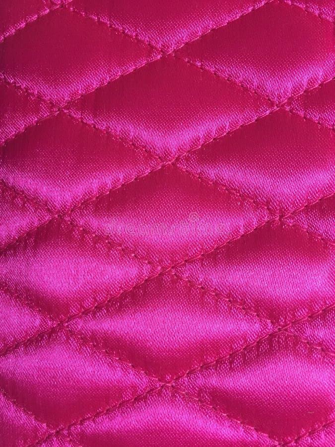 Diamantpatroon in roze stof wordt gestikt die stock foto