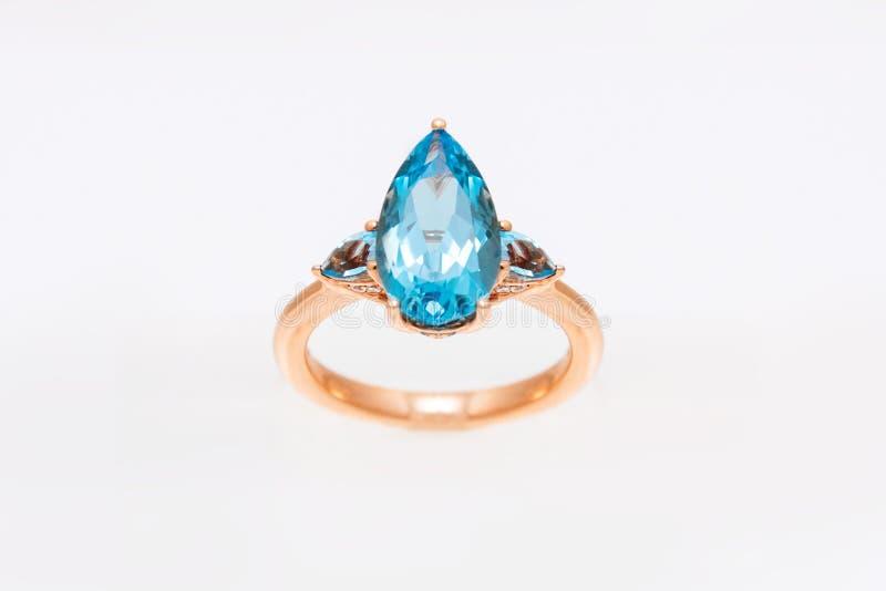 Diamantring mit blauen kostbaren Edelsteinen Gelber goldener Ring auf hellem Hintergrund Modeluxuszus?tze lizenzfreie stockfotos