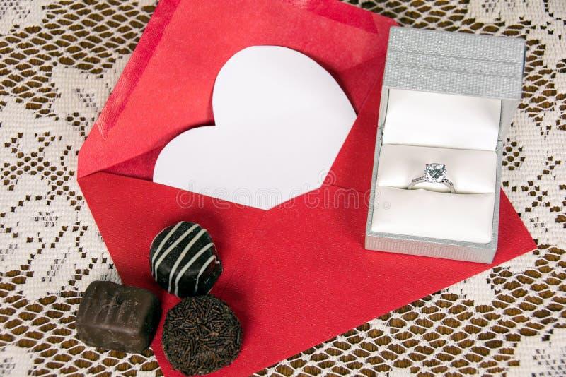 Diamantring und -schokoladen auf rotem Umschlag lizenzfreie stockfotos