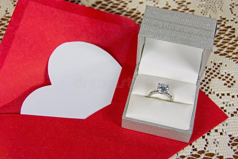 Diamantring und weißes Herz im Umschlag stockbilder