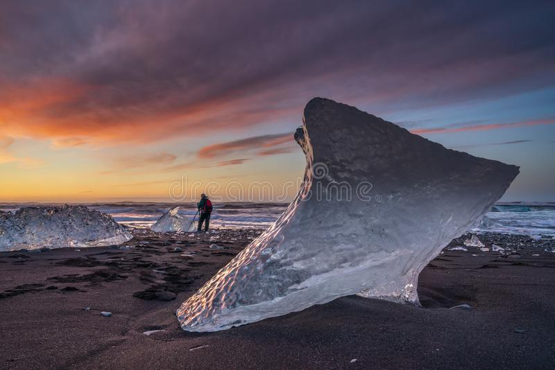 Sunrise at Diamond beach, near Jokulsarlon glacier lagoon, with a photographer stock image