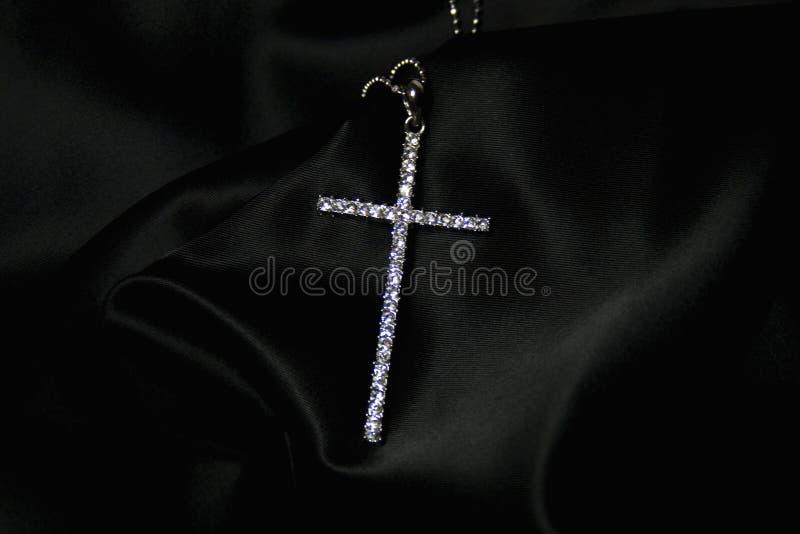 Diamond cross on black silk royalty free stock image