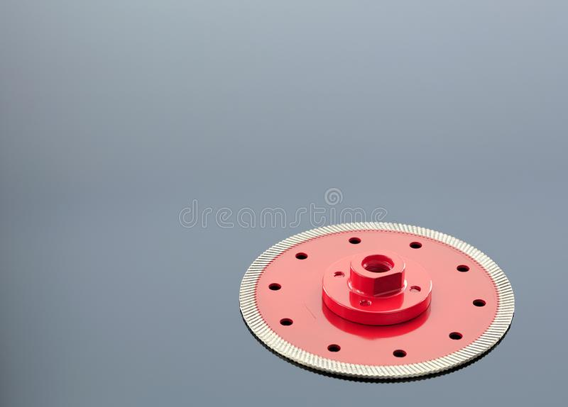 Diamond cutting wheel is red with a threaded nut on the mirror surface of a gray background with a slight gradient. Diamond cutting wheel is red with a threaded royalty free stock images