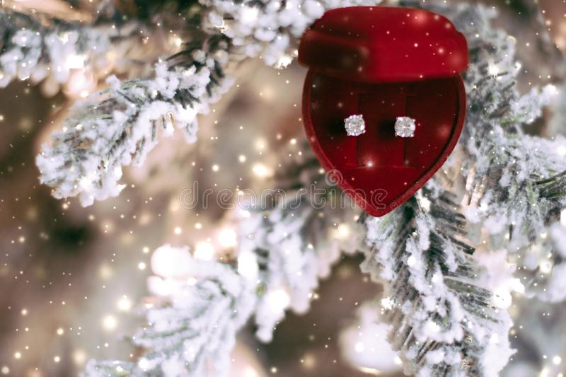 Diamond earrings in heart shaped jewellery gift box on Christmas tree, love present for New Years Eve, Valentines Day and winter. Timeless luxury, romantic and stock photo