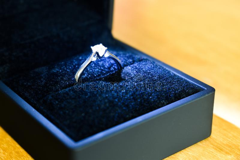 Diamond engagement ring in blue ring box. On wooden table royalty free stock photos