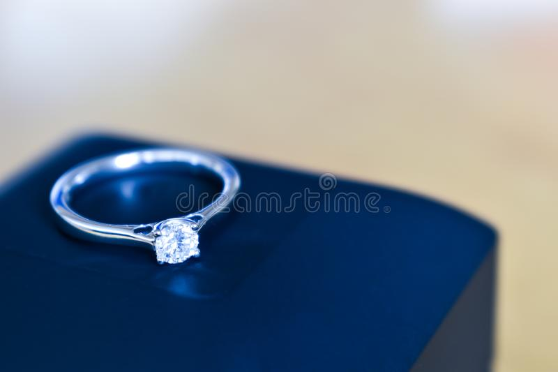 Diamond engagement ring on top of blue ring box. On wooden table stock photos