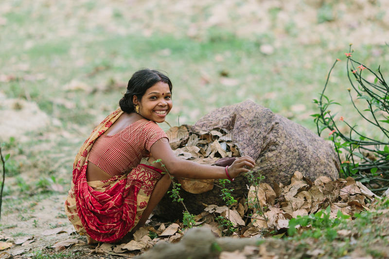 DIAMOND HARBOR, INDIA - APRIL 01, 2013 : Pore rural Indian woman with a big smile in the red-yellow sari collects falling leaves. From the ground stock photo