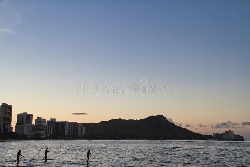 Diamond Head in the Morning with Paddle Boarders. A very early morning image of Diamond Head volcano from Waikiki Beach, Hawaii with three paddle boarders stock photos