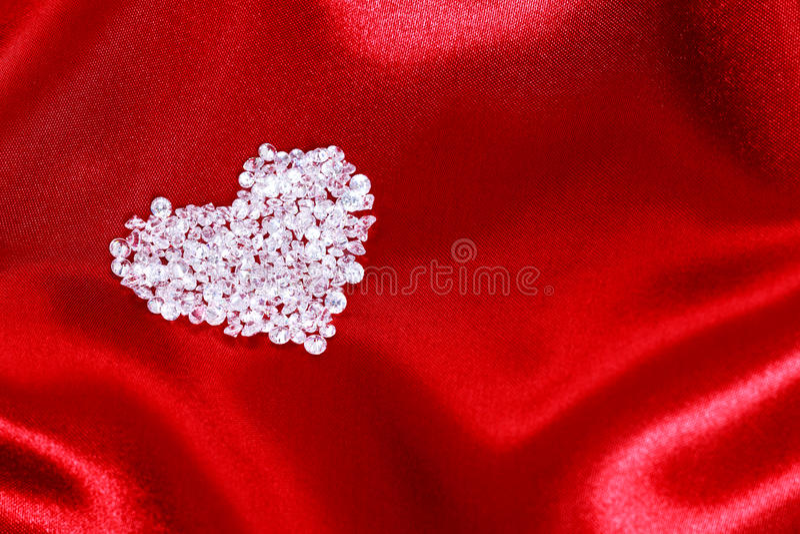 Diamond heart on red satin stock photos