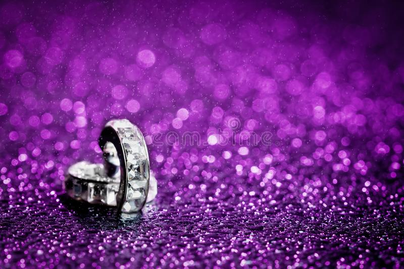 Diamond in purple water drops. Pair of diamond earrings shot against ultra violet gelled flashlight background with sprinkles of water sprayed from above with