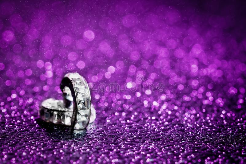 Diamond in purple water drops. Pair of diamond earrings shot against ultra violet gelled flashlight background with sprinkles of water sprayed from above with stock photo