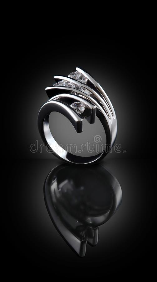 Diamond ring on black background. Silver ring with diamonds on black background royalty free stock photography