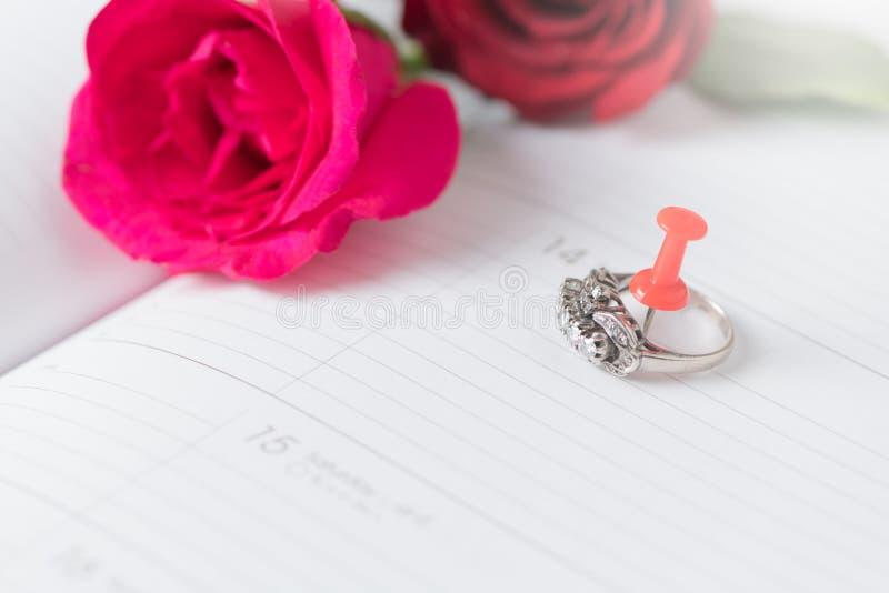 Diamond ring on calendar book with pink rose stock photos