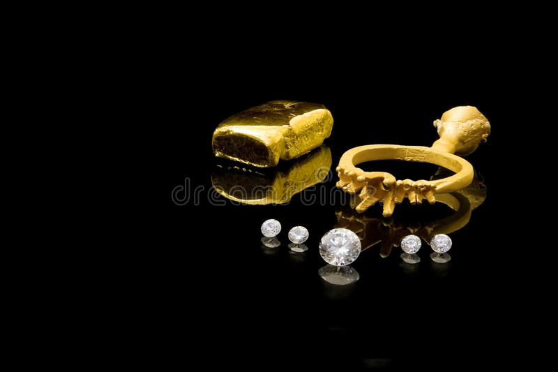 Diamond Ring Construction. Newly cast gold ring and ingot, with diamonds ready for setting royalty free stock photos