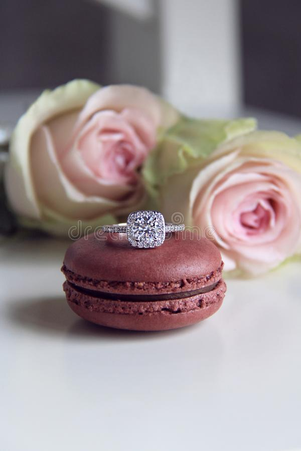 Diamond ring on macaron and roses background stock image