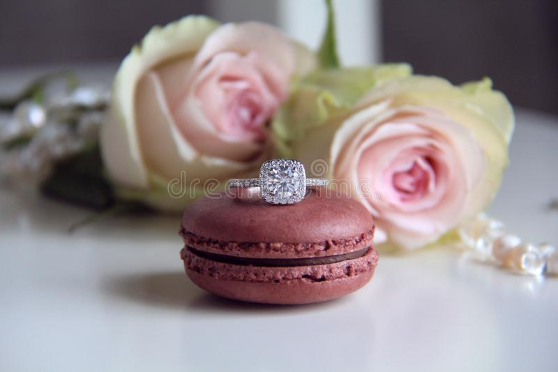 Diamond ring on macaron and roses background royalty free stock photography