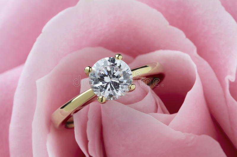 Diamond Ring and Rose. Diamond ring resting in a pink rose flower stock photos
