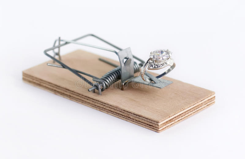 Diamond ring wedding gift on mouse trap. On white stock photography
