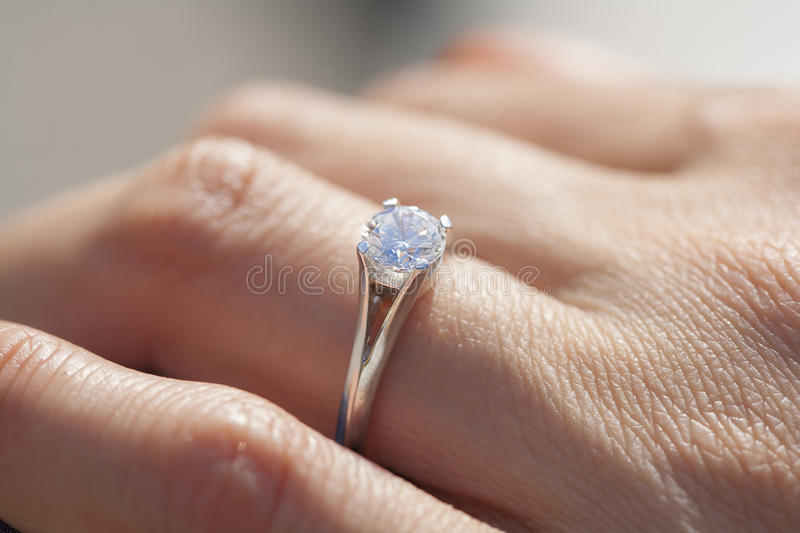 A diamond ring. A woman hand wearing a diamond ring stock images
