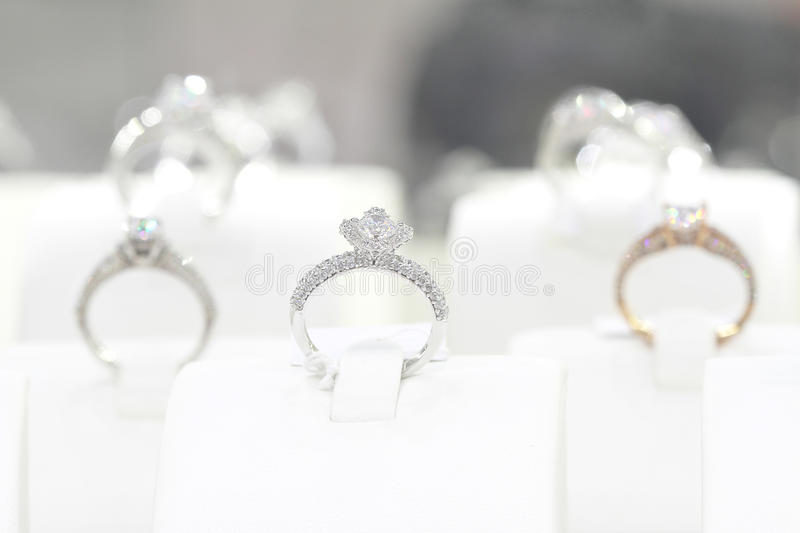 Diamond rings. Diamond engagement rings at a shops display photographed under ambient lighting with a gold diamond ring in frame royalty free stock images