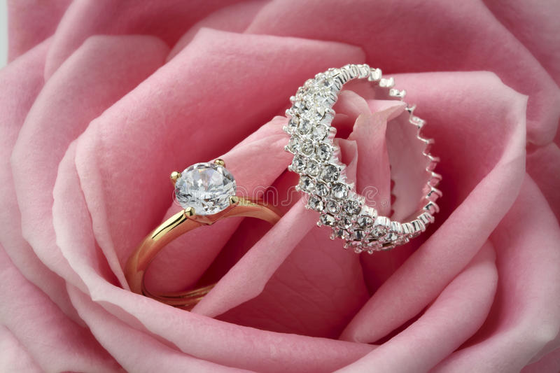 Diamond Rings and Rose. Diamond rings resting in a pink rose flower royalty free stock photos
