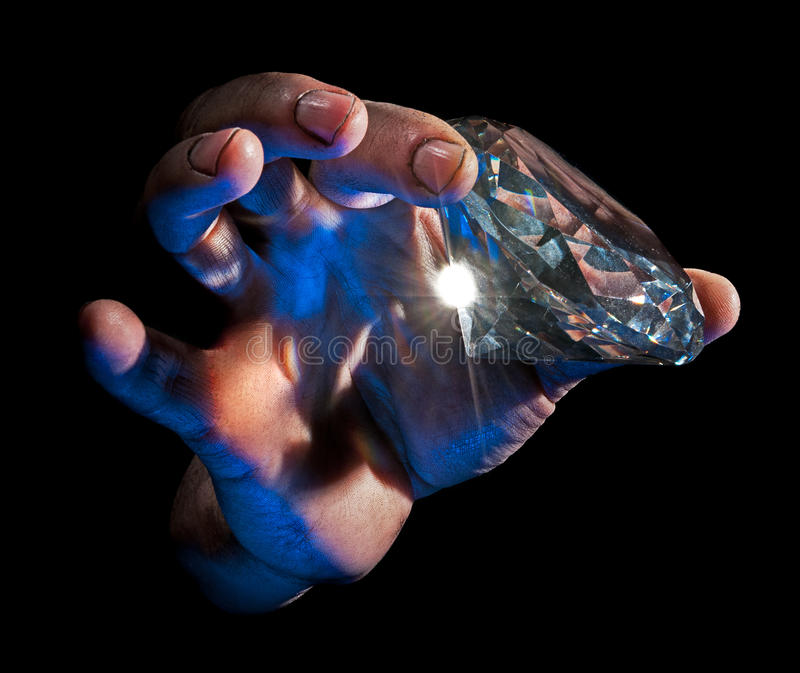 Diamond in the Rough. Dirty male hand hold diamond against black background - blue lit from underside, natural flare stock photography