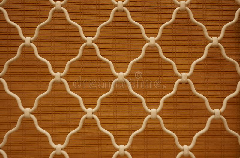 Diamond shape of white curved wrought iron steel on the lattice window, brown bamboo curtain background, vintage style lattice. Work for house decoration royalty free stock photography
